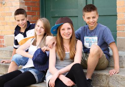 Jugendliche  warten auf einem Treppenaufgang auf das Dorfshuttle